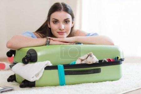 Photo pour Belle jeune femme brune qui emballe sa valise et regarde la caméra, emballe le concept de bagages - image libre de droit
