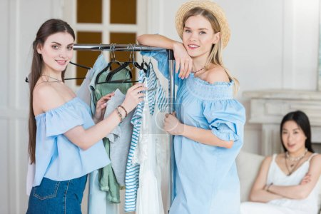 Photo for Smiling young women choosing clothes together indoors - Royalty Free Image