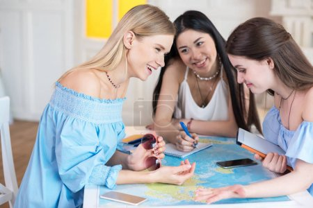 women travelers looking at world map