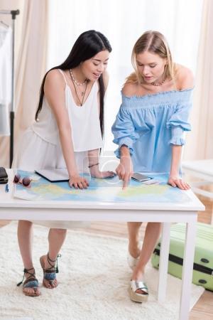 Photo pour Les voyageurs jeunes belles femmes regardant la carte du monde en salle, best filles amis - image libre de droit