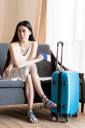 Photo pour Asiatique femme voyageur assis sur canapé avec valise et passeport, emballage bagages - image libre de droit