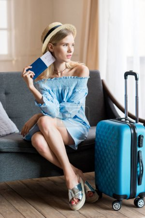 Photo for Caucasian woman traveler sitting on sofa with suitcase and passport, packing luggage - Royalty Free Image