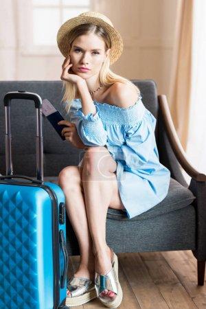 Photo pour Femme caucasienne voyageur assis sur le canapé avec valise et passeport, bagages d'emballage - image libre de droit