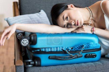 Photo pour Belle asiatique femme voyageur couché sur canapé avec valise, emballage bagages - image libre de droit