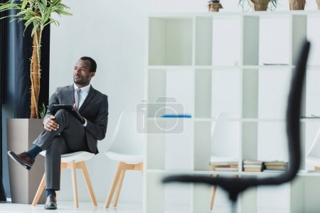 Photo for Pensive african american businessman sitting on chair in office and looking away - Royalty Free Image