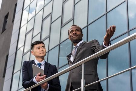 Photo pour Réunion de l'équipe des affaires multiculturelles en plein air près d'immeuble de bureaux - image libre de droit