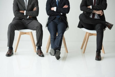 Photo for Low section of businessmen sitting on chairs isolated on white, businessmen group concept - Royalty Free Image