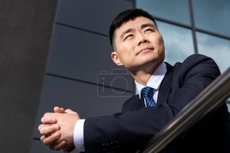 Photo pour Portrait de succès asiatique homme d'affaires debout à l'immeuble de bureaux et regardant loin - image libre de droit