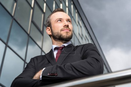 Photo for Portrait of successful handsome businessman standing at office building and looking away - Royalty Free Image