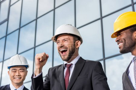 Photo for Multiethnic group of excited professional architects in helmets outside office building, architects meeting concept - Royalty Free Image