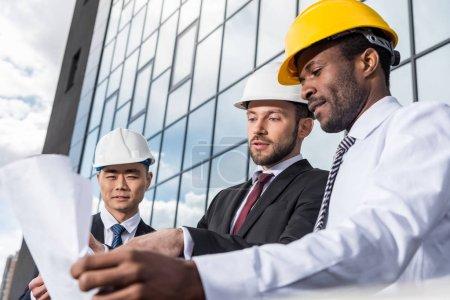 Photo pour Groupe multiethnique d'architectes professionnels dans les casques travaillant avec le plan à l'extérieur du bâtiment moderne - image libre de droit