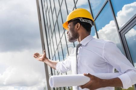Photo for Low angle view of professional architect in hard hat holding blueprint outside modern building - Royalty Free Image