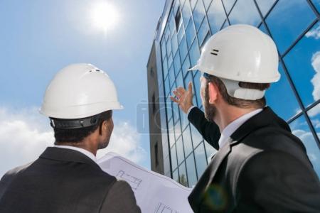 Photo pour Vue faible angle d'architectes professionnels en casques avec plan de travail - image libre de droit