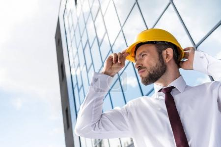 Photo for Side view of confident professional architect in hard hat against building - Royalty Free Image