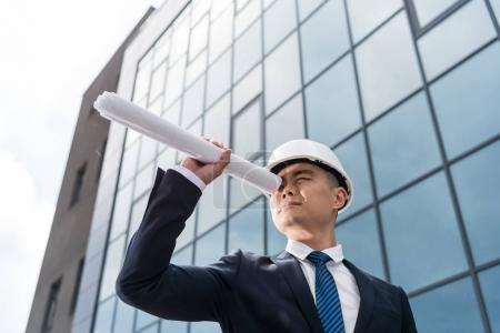 Photo pour Portrait de l'architecte dans un casque regardant à travers le plan d'action dans la main - image libre de droit