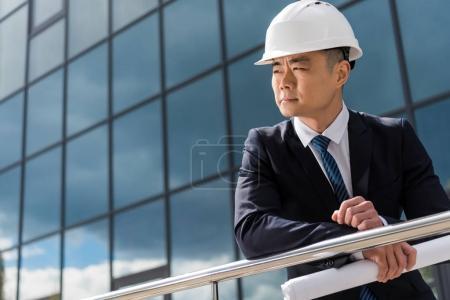 Photo pour Portrait d'architecte professionnel en casque rigide tenant un plan directeur - image libre de droit