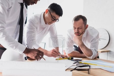 Photo for Team of architects working on plan together in modern office - Royalty Free Image