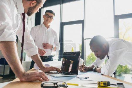Photo pour Architectes professionnels dans l'habillement formel travaillant au bureau moderne, groupe d'hommes d'affaires - image libre de droit