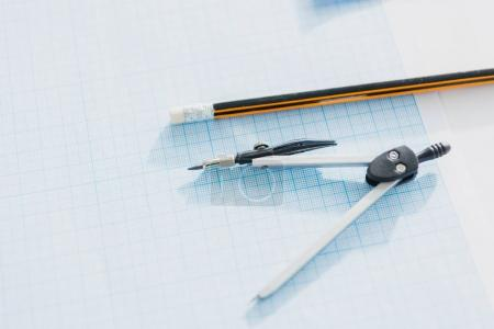 Compasses and pencil on empty blueprint