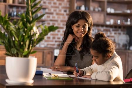 Photo for Smiling mother looking at cute little daughter doing homework, homework help concept - Royalty Free Image