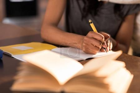 Photo pour Vue partielle de la femme assise à table et écrivant dans un cahier à la maison - image libre de droit