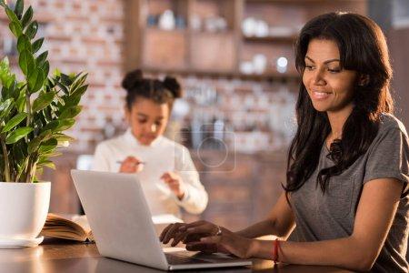 Photo pour Vue latérale de la femme souriante tapant sur ordinateur portable avec sa fille faisant ses devoirs à proximité - image libre de droit