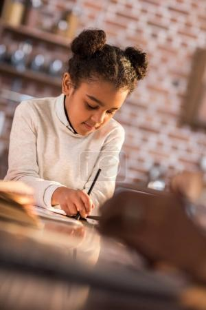 Photo pour Portrait d'une petite fille concentrée faisant ses devoirs à la maison - image libre de droit