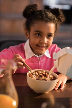 Photo for Portrait of smiling little girl having breakfast at home - Royalty Free Image