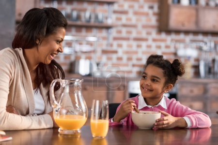 Photo for Portrait of mother and daughter having breakfast together at home - Royalty Free Image