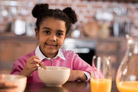 Photo pour Portrait d'une petite fille souriante prenant le petit déjeuner à la maison - image libre de droit