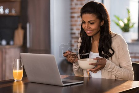 Photo for Young african american woman having breakfast and using laptop at kitchen - Royalty Free Image