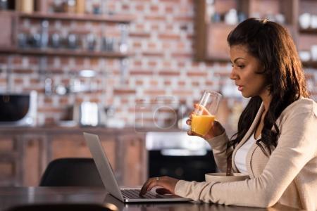 Foto de Mujer afroamericana joven desayunando y usando portátil en la cocina - Imagen libre de derechos