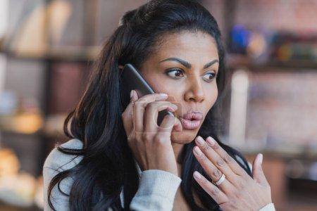 Photo pour Portrait de surpris jeune femme afro-américaine parler sur smartphone à la maison - image libre de droit