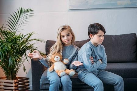 Photo pour Adorable fille tenant ours en peluche tandis que offensé garçon assis sur canapé à la maison - image libre de droit