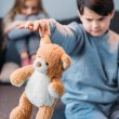 Boy holding teddy bear while offended girl sitting...