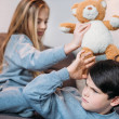 Boy and girl playing with teddy bear and sitting o...