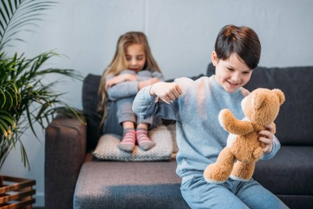 Boy punching teddy bear