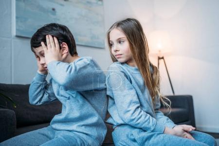 Siblings in pajamas at home