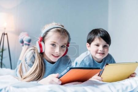 Photo for Girl in headphones and little boy using digital tablets while lying on bed - Royalty Free Image