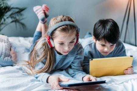 Photo for Little girl in headphones and boy using digital tablets while lying on bed - Royalty Free Image