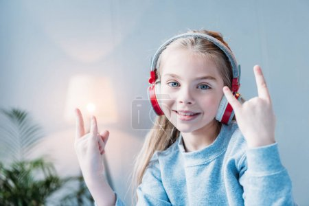 Photo for Portrait of smiling little girl in headphones showing rock signs - Royalty Free Image