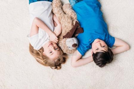little boy and girl lying on carpet
