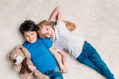 Little boy and girl lying on carpet