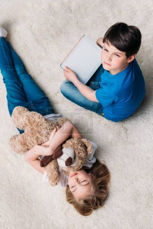 Photo for Little girl with teddy bear and boy with digital tablet on carpet at home - Royalty Free Image