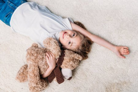 Photo pour Petite fille tenant ours en peluche et regardant la caméra tout en étant couché sur le tapis à la maison - image libre de droit