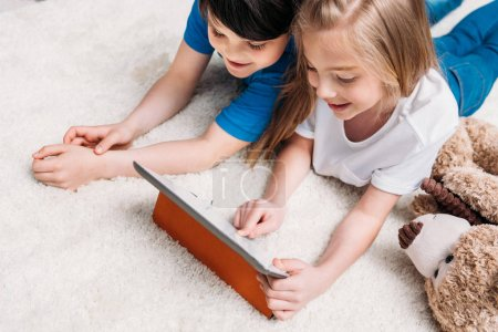 Photo for Little boy and girl playing with digital tablet while lying on carpet at home - Royalty Free Image