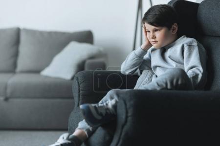 Photo pour Cher petit garçon assis sur canapé à la maison - image libre de droit