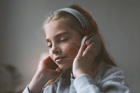 Photo for Pensive kid girl listening music in headphones with eyes closed - Royalty Free Image