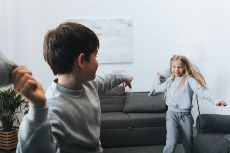 boy and girl pillow fight at home