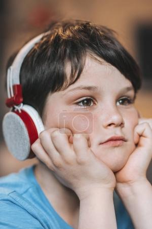 pensive boy listening music in headphones